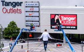High-wire artist Nik Wallenda performs a stunt outside the new Tanger Outlets at Foxwoods on May 22, 2015