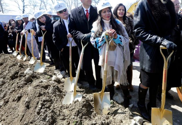 Tribal Council member Winnie Johnson Graham, foreground, holds a shovel along with others during an official groundbreaking, Tuesday, April 5, 2016, in Taunton, Mass., where the Mashpee Wampanoag tribe will build a resort casino that it hopes will become Massachusetts' first Las Vegas-style resort. The First Light casino, hotel and entertainment complex will be built on a 151-acre industrial park that's part of the Cape Cod-based tribe's recently designated federal reservation. (AP Photo/Elise Amendola)
