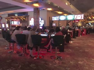 Seats, at least two rows, on either side of two sets of dealers. Players can choose to play baccarat, roulette, or other games the live dealers are dealing. Games are shown live on the screens above the dealers.
